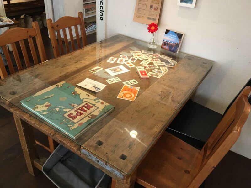 木のテーブルの真ん中がガラス張りで中にカードがある