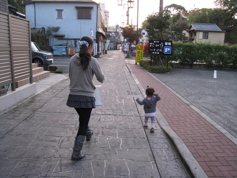 道路を歩く女性とこどもの後姿