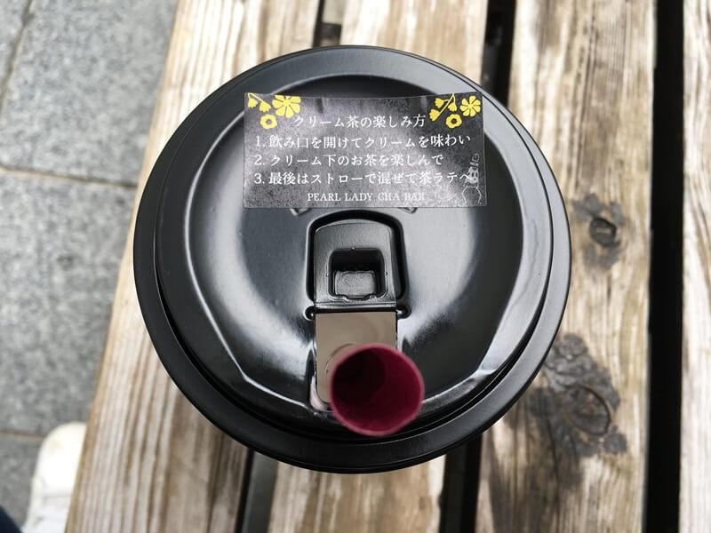 カップにストローがささり、木の椅子に置かれている